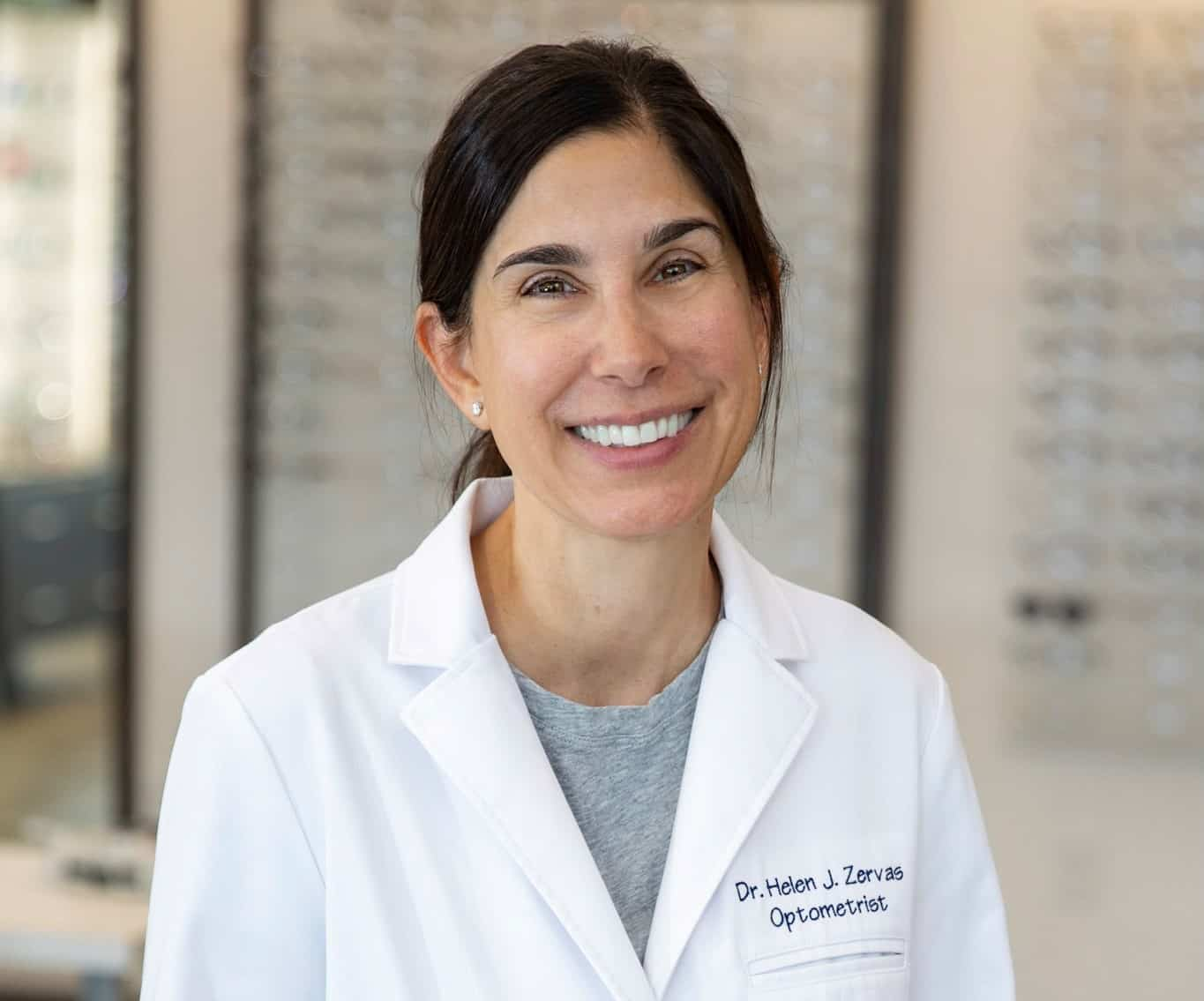 Dr. Helen J. Zervas of Family Eye Care standing smiling for the camera in their Bristol Optometry office.