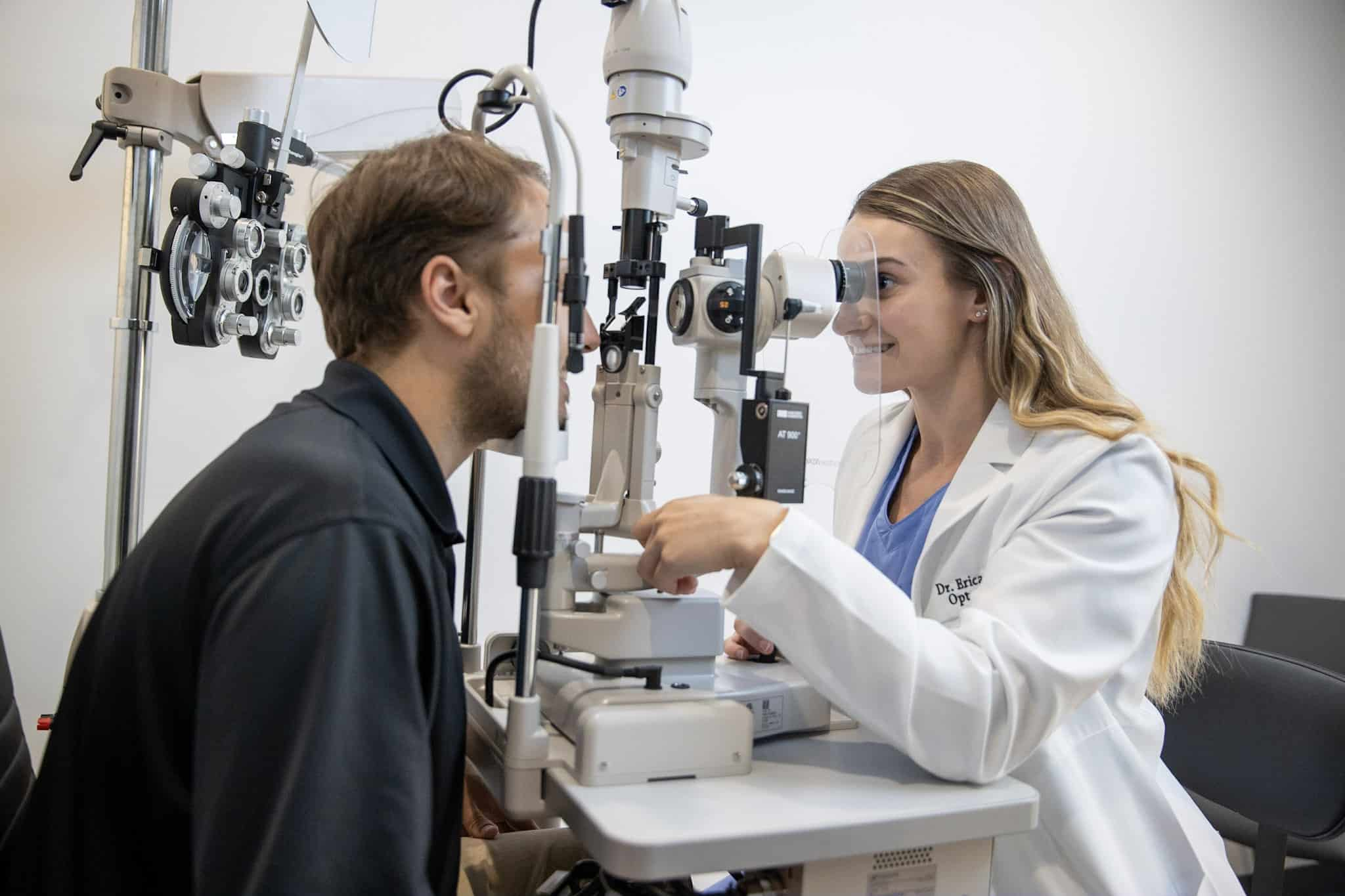 Dr. Erika Stokes of Family Eye Care performing a slit lamp examination on a male patient to examine his eye health.