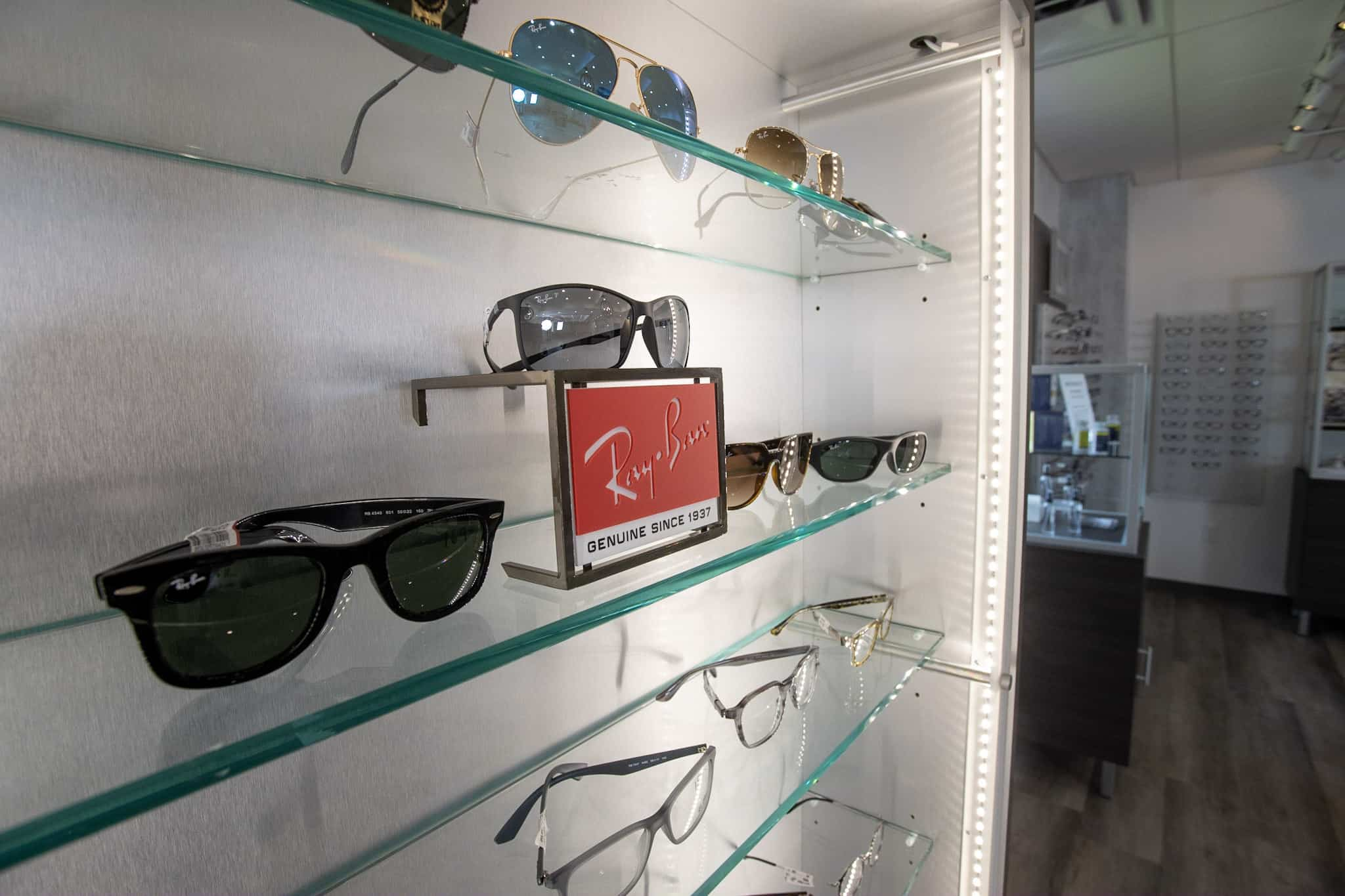 Ray Ban prescription sunglasses display positioned on glass shelves of Family Eye Care Bristol Optometry office.